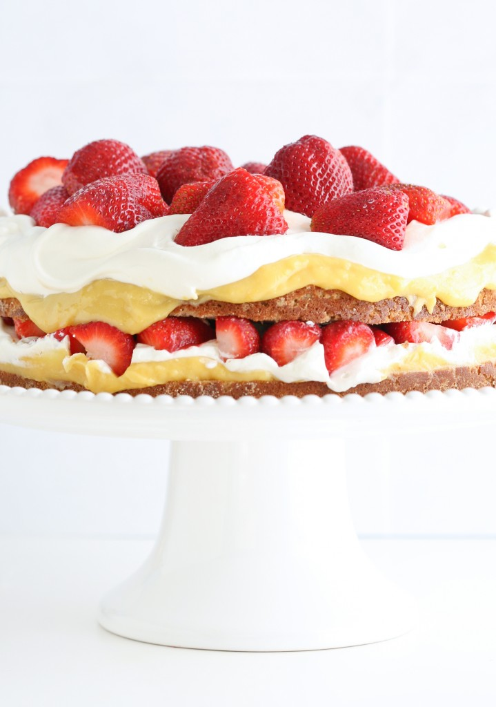 Grain free and gluten free coconut cake topped with honey-sweetened lemon curd, strawberries and billows of whipped cream.