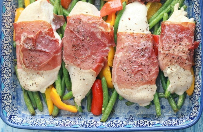 For this prosciutto wrapped chicken breast recipe, I wrapped thin slices of prosciutto around chicken breasts and laid them on a bed of green beans and